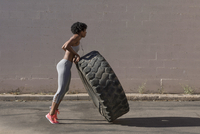 Full length of woman lifting tire truck while exercising against wall