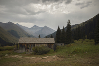 Log cabin at Ghost Town against mountains and cloudy sky 11100074291| 写真素材・ストックフォト・画像・イラスト素材|アマナイメージズ