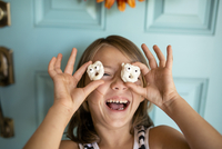 Close-up of cheerful girl holding anthropomorphic cookies against face 11100074300| 写真素材・ストックフォト・画像・イラスト素材|アマナイメージズ