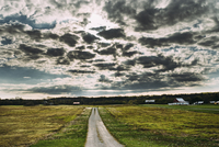 Scenic view of country road against cloudy sky