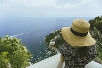 Woman wearing straw hat while looking at view 11100074865| 写真素材・ストックフォト・画像・イラスト素材|アマナイメージズ