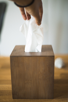 Cropped hand of person removing tissue paper from box on table