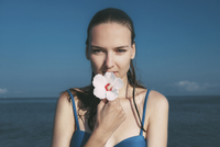 Portrait of woman holding hibiscus against sea and sky 11100075053| 写真素材・ストックフォト・画像・イラスト素材|アマナイメージズ