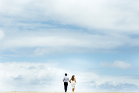 Rear view of newlywed couple running at beach against cloudy sky 11100075829| 写真素材・ストックフォト・画像・イラスト素材|アマナイメージズ