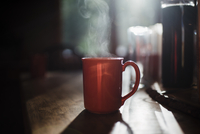 Close-up of steam emitting from coffee cup on table at home 11100076283| 写真素材・ストックフォト・画像・イラスト素材|アマナイメージズ