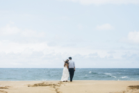 Rear view of newlywed couple standing at beach against sky 11100076334| 写真素材・ストックフォト・画像・イラスト素材|アマナイメージズ