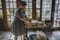 Side view of female potter making clay pot at pottery 11100077229| 写真素材・ストックフォト・画像・イラスト素材|アマナイメージズ