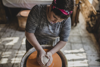 High angle view of female potter making clay pot at pottery 11100077231| 写真素材・ストックフォト・画像・イラスト素材|アマナイメージズ
