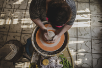 High angle view of female craftsperson making clay pot at pottery 11100077232| 写真素材・ストックフォト・画像・イラスト素材|アマナイメージズ