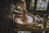 Midsection of female potter making clay pot out of mud using pottery wheel 11100077235| 写真素材・ストックフォト・画像・イラスト素材|アマナイメージズ