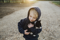 High angle view of cute boy embracing cat at park 11100077430| 写真素材・ストックフォト・画像・イラスト素材|アマナイメージズ