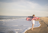 Rear view of teenage girl holding American Flag while running at beach against sky 11100077993| 写真素材・ストックフォト・画像・イラスト素材|アマナイメージズ