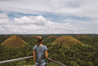 Rear view of woman looking at Chocolate Hills while standing by railing against cloudy sky 11100079149| 写真素材・ストックフォト・画像・イラスト素材|アマナイメージズ
