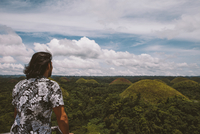 Rear view of man looking at Chocolate Hills while standing by railing against cloudy sky 11100079150| 写真素材・ストックフォト・画像・イラスト素材|アマナイメージズ