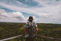 Rear view of man with backpack looking at Chocolate Hills while standing by railing 11100079151| 写真素材・ストックフォト・画像・イラスト素材|アマナイメージズ