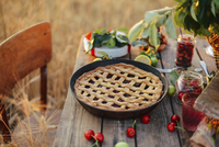 Close-up of cherry pie in container on wooden table 11100079292| 写真素材・ストックフォト・画像・イラスト素材|アマナイメージズ