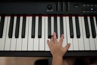 Cropped hand of boy playing piano at home