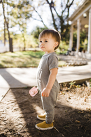 Side view of cute baby boy looking away while standing on dirt 11100080378| 写真素材・ストックフォト・画像・イラスト素材|アマナイメージズ