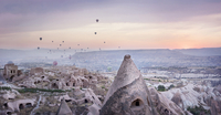 Hot air balloons flying over landscape against cloudy sky during sunset 11100080512| 写真素材・ストックフォト・画像・イラスト素材|アマナイメージズ