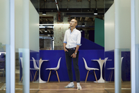Full length of thoughtful businessman standing against table and chairs at office cafeteria 11100083434| 写真素材・ストックフォト・画像・イラスト素材|アマナイメージズ