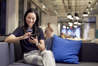 Smiling businesswoman using mobile phone while sitting on sofa at office 11100083540| 写真素材・ストックフォト・画像・イラスト素材|アマナイメージズ