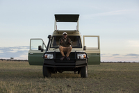 Portrait of man gesturing while sitting on vehicle at Serengeti National Park against sky 11100083876| 写真素材・ストックフォト・画像・イラスト素材|アマナイメージズ