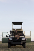 Side view of man sitting on vehicle at Serengeti National Park against sky 11100083878| 写真素材・ストックフォト・画像・イラスト素材|アマナイメージズ