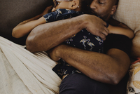High angle view of father embracing daughter while sleeping on sofa at home