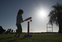 Side view of girl playing with t-ball at park during summer