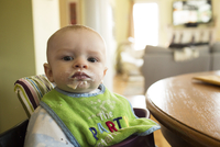 Close-up portrait of baby boy sitting on high chair by table at home
