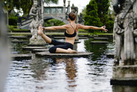 Full length of woman practicing yoga on platform amidst pond at park