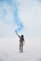 Rear view of man holding smoke bomb while standing on Bonneville Salt Flats against sky