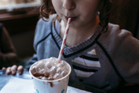 Midsection of playful girl blowing bubbles in chocolate milk at home 11100085428| 写真素材・ストックフォト・画像・イラスト素材|アマナイメージズ