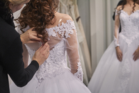 Side view of designer assisting bride in trying wedding dress at store