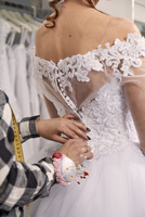 Midsection of designer assisting bride in trying wedding dress at store 11100085526| 写真素材・ストックフォト・画像・イラスト素材|アマナイメージズ