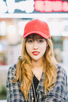 Portrait of confident young woman wearing cap in city