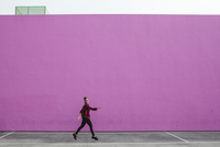 Full length of woman jumping on footpath against pink wall 11100085621| 写真素材・ストックフォト・画像・イラスト素材|アマナイメージズ
