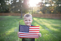 Portrait of smiling boy holding American flag while standing on field in yard 11100085647| 写真素材・ストックフォト・画像・イラスト素材|アマナイメージズ