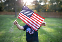 Boy showing American flag while standing on field in yard 11100085648| 写真素材・ストックフォト・画像・イラスト素材|アマナイメージズ