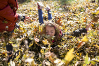 Siblings playing in leaves on field in yard during autumn 11100085669| 写真素材・ストックフォト・画像・イラスト素材|アマナイメージズ