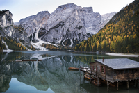 Cottage in calm lake by mountains against sky during winter 11100085689| 写真素材・ストックフォト・画像・イラスト素材|アマナイメージズ