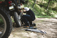 Biker repairing motorcycle in forest