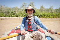 Portrait of senior man kayaking in river