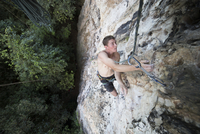 High angle view of shirtless hiker rock climbing