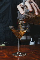 Midsection of bartender pouring alcohol in martini glass on table 11100086166| 写真素材・ストックフォト・画像・イラスト素材|アマナイメージズ