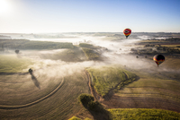 Aerial view of hot air balloons flying over landscape against sky during sunny day 11100088697| 写真素材・ストックフォト・画像・イラスト素材|アマナイメージズ