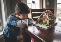 Happy boy looking at gingerbread house on wooden table during Christmas 11100089158| 写真素材・ストックフォト・画像・イラスト素材|アマナイメージズ
