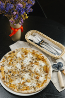 High angle view of pizza in plate with cutleries and napkin by flower vase on table 11100090596| 写真素材・ストックフォト・画像・イラスト素材|アマナイメージズ