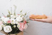 Cropped hand of woman holding sweet food by flower vase against wall 11100090621| 写真素材・ストックフォト・画像・イラスト素材|アマナイメージズ