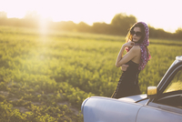Portrait of woman wearing sunglasses standing by car on grassy field against sky during sunset 11100090757| 写真素材・ストックフォト・画像・イラスト素材|アマナイメージズ